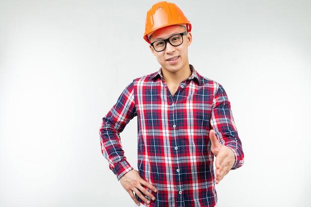 Homem de óculos com um capacete laranja para segurança em um branco