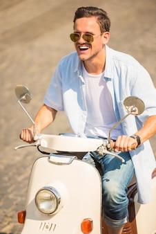 Homem de óculos de sol é andar de scooter ao longo da rua.