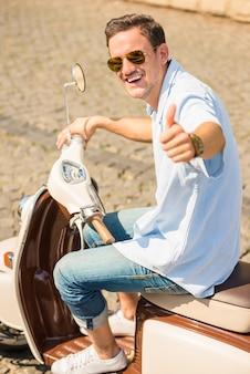Homem de óculos de sol está sentado na scooter e sorrindo.