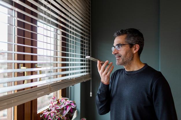 Homem de óculos e cabelos grisalhos enviando uma mensagem de voz pelo telefone enquanto olha pela janela de sua casa