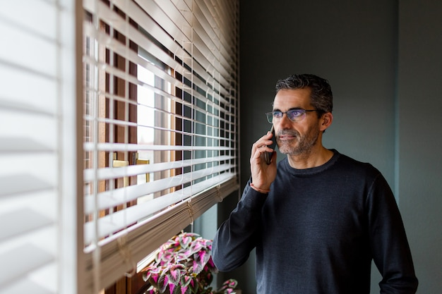 Homem de óculos e cabelos grisalhos falando ao telefone enquanto olha pela janela de sua casa