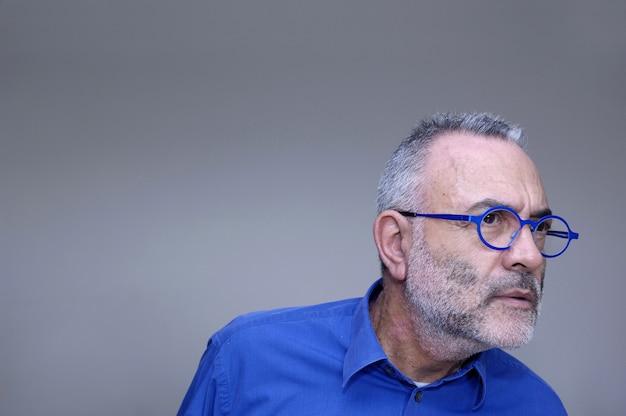 Homem de óculos e camisa azul olhando,