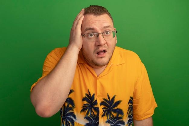 Homem de óculos e camisa laranja parecendo confuso com a mão na cabeça por engano em pé sobre uma parede verde