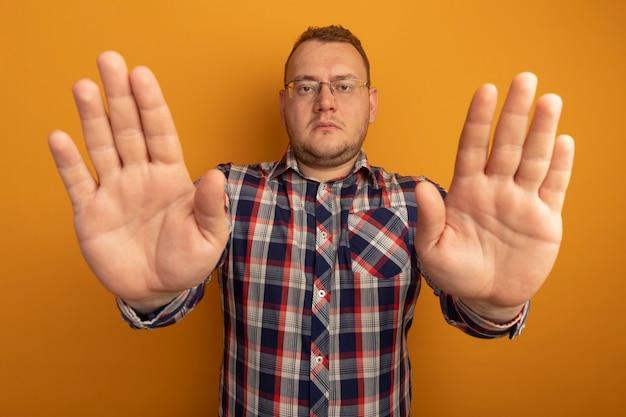 Homem de óculos e camisa xadrez fazendo gesto de parada com as mãos abertas com rosto sério em pé sobre a parede laranja