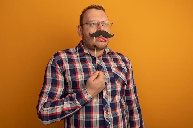 Homem de óculos e camisa xadrez segurando um bigode engraçado no palito, mostrando a língua, em pé sobre a parede laranja