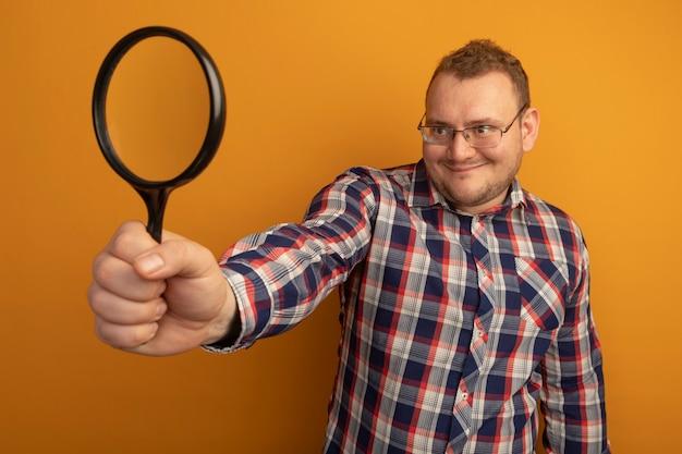 Homem de óculos e camisa xadrez segurando uma lupa e olhando para ela com um sorriso no rosto em pé sobre uma parede laranja