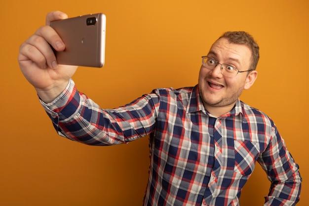 Homem de óculos e camisa xadrez usando smartphone fazendo selfie sorrindo alegremente em pé sobre a parede laranja