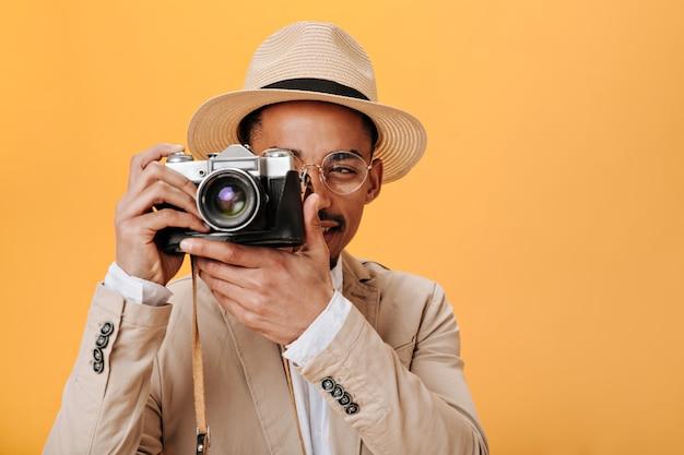 Homem de óculos e chapéu posando na parede laranja com câmera retro