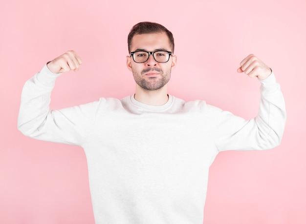 Homem de óculos em boa forma mostra seus músculos isolados na parede rosa