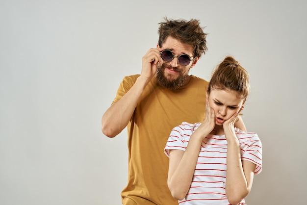 Homem de óculos escuros ao lado de mulher em diversão de estúdio de moda de comunicação de emoções de camiseta listrada.