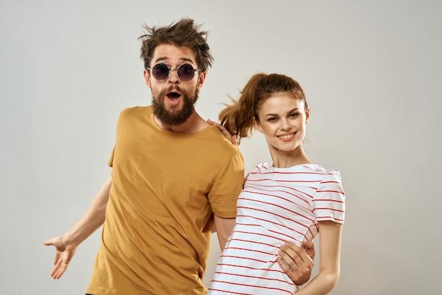 Homem de óculos escuros ao lado de uma mulher de camiseta listrada
