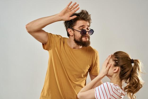 Homem de óculos escuros ao lado de uma mulher em uma camiseta listrada emoções comunicação moda estúdio diversão
