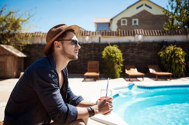 Homem de óculos escuros e chapéu bebendo coquetel, sentado perto da piscina