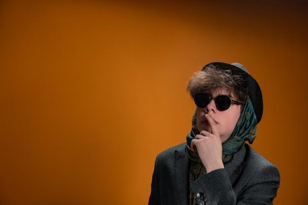 Homem de óculos escuros e chapéu em fundo laranja e preto