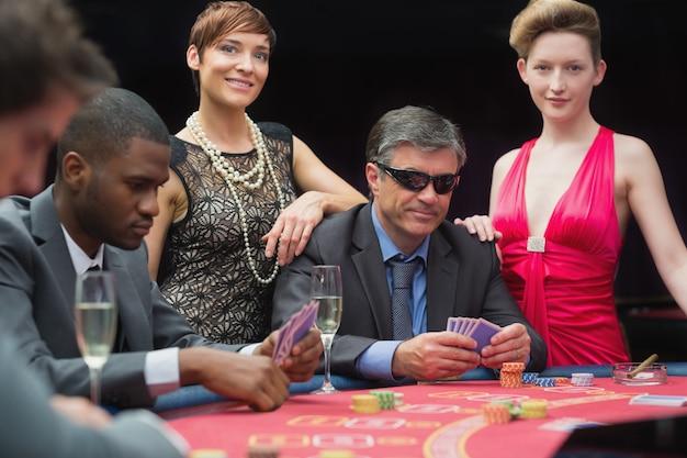 Homem de óculos escuros jogando poker com duas mulheres de cada lado