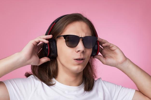 Homem de óculos escuros ouve música com fones de ouvido e dança