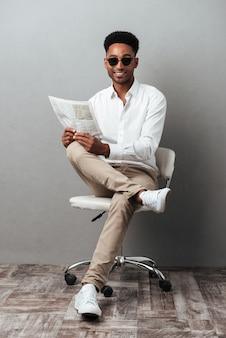Homem de óculos escuros, segurando o jornal enquanto está sentado em uma cadeira
