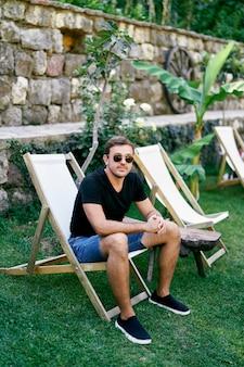 Homem de óculos escuros sentado em uma cadeira dobrável em um gramado verde perto de uma parede de pedra