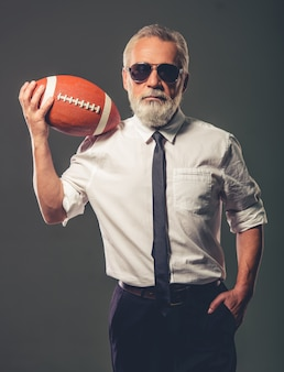 Homem de óculos está segurando uma bola de futebol.