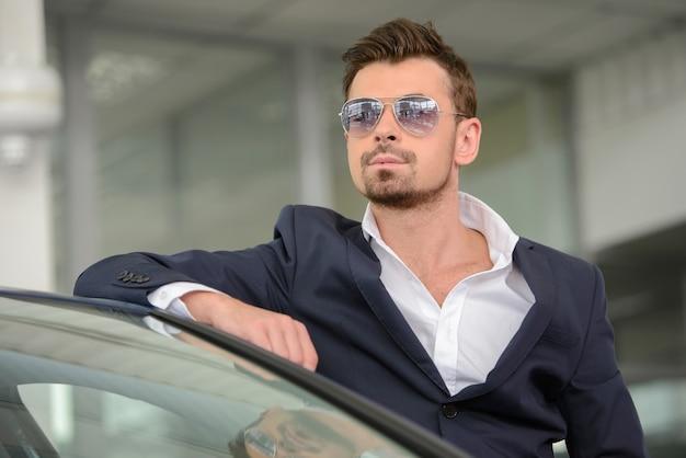 Homem de óculos, inclinando-se para o carro e olhando para a câmera.