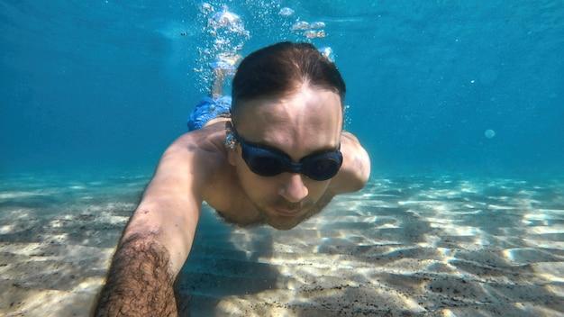 Homem de óculos, nadando sob as águas azuis e transparentes do mar mediterrâneo. segurando a câmera
