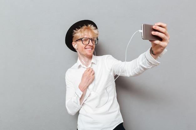 Homem de óculos, ouvindo música enquanto faz selfie.