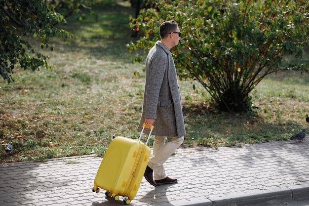 Homem de óculos pretos, com uma mala amarela de calça bege, com um casaco cinza andando no parque.