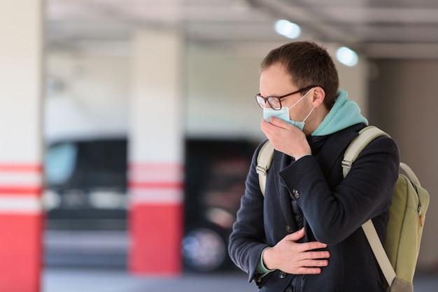Homem de óculos se sentindo doente no estacionamento, tossindo, usando máscara protetora contra doenças infecciosas transmissíveis e coronavírus