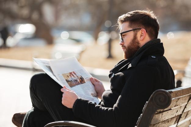 Homem de óculos, sentado e lendo jornal na cidade
