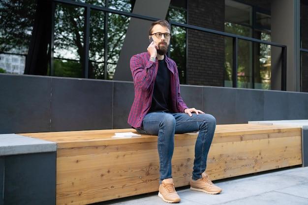 Homem de óculos, sentado no banco de madeira e falando no telefone