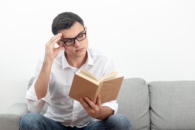 Homem de óculos, sentado no sofá e lendo o livro
