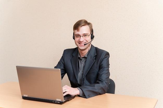 Homem de óculos trabalha para laptop