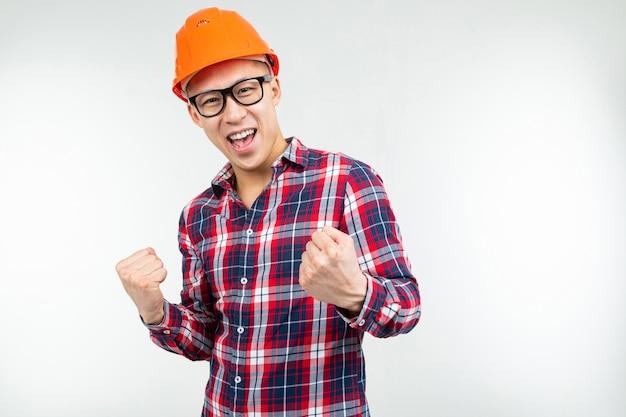 Homem de óculos, um capacete laranja do construtor em um fundo branco