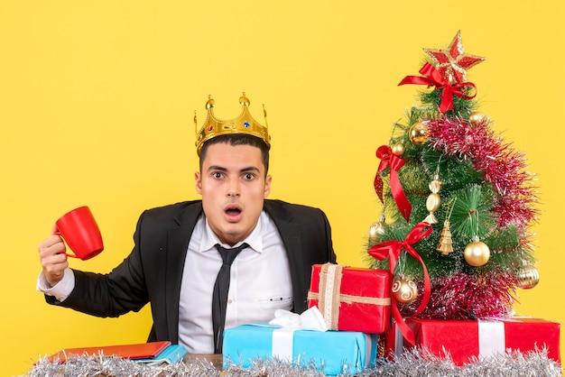 Homem de olhos arregalados de frente com a coroa segurando um copo sentado perto da árvore de natal e presentes