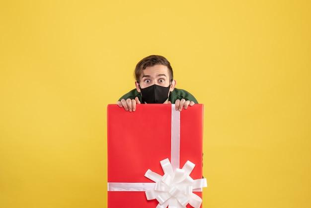Homem de olhos arregalados de frente com máscara escondida atrás de uma grande caixa de presente amarela