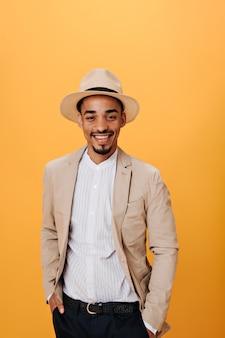 Homem de olhos castanhos com camisa, jaqueta bege e chapéu sorrindo na parede laranja