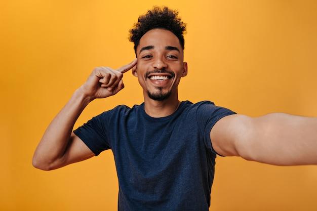 Homem de olhos castanhos com camiseta azul e sorriso fazendo selfie na parede laranja