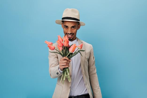 Homem de olhos castanhos com chapéu segurando tulipas cor de rosa na parede azul