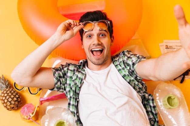 Homem de olhos castanhos vestindo camiseta branca e camisa xadrez tira os óculos escuros e tira uma selfie no colchão inflável.