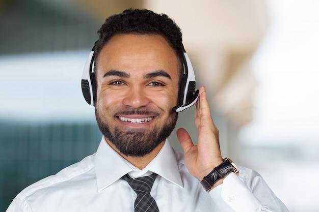 Homem de operador de centro de chamada com fones de ouvido trabalhando