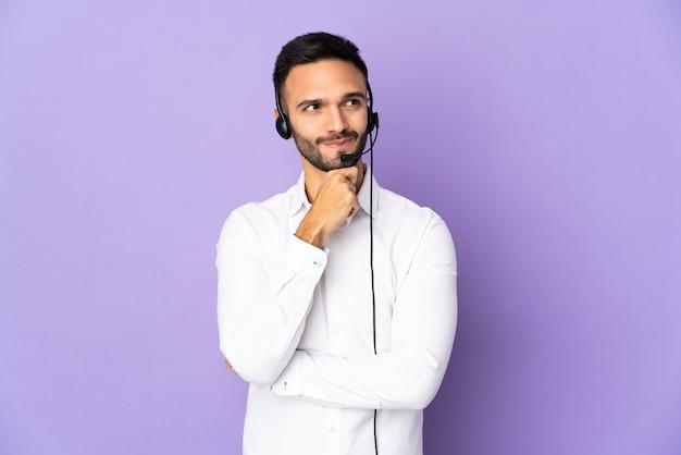 Homem de operador de telemarketing trabalhando com um fone de ouvido isolado em um fundo roxo, tendo dúvidas e pensando