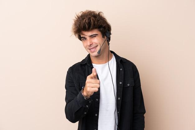 Homem de operador de telemarketing trabalhando com um fone de ouvido sobre a parede isolada aponta o dedo para você