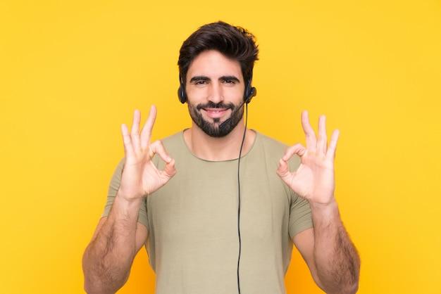 Homem de operador de telemarketing trabalhando com um fone de ouvido sobre parede amarela isolada, mostrando um sinal de ok com os dedos