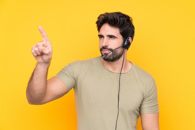 Homem de operador de telemarketing trabalhando com um fone de ouvido sobre parede amarela isolada, tocando na tela transparente