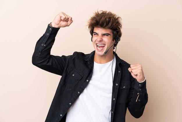 Homem de operador de telemarketing trabalhando com um fone de ouvido sobre parede isolada comemorando uma vitória