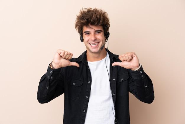 Homem de operador de telemarketing trabalhando com um fone de ouvido sobre parede isolada, orgulhoso e satisfeito