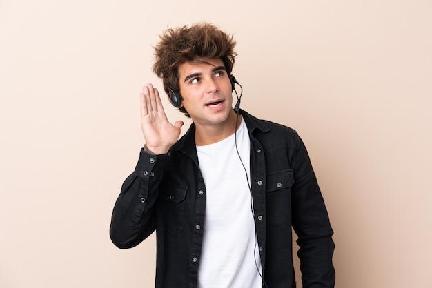 Homem de operador de telemarketing trabalhando com um fone de ouvido sobre parede isolada, ouvindo algo