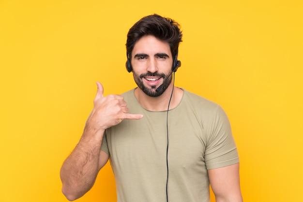 Homem de operador de telemarketing trabalhando com um fone de ouvido sobre parede isolada