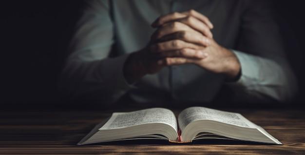 Homem de oração entregando a bíblia no quarto escuro