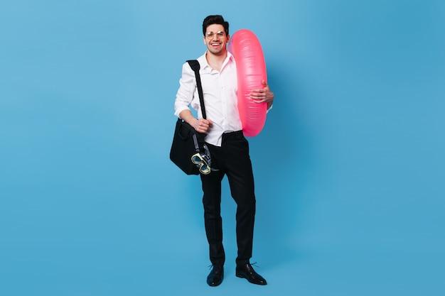 Homem de ótimo humor mantém um círculo inflável. cara de camisa e calça posando com máscara de mergulho no espaço azul.